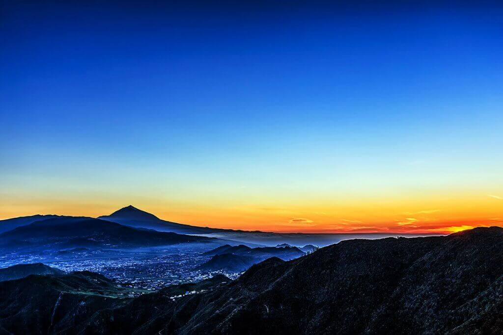 Sunset in mountains and blue sky with fog and Teide volcano on background in Tenerife